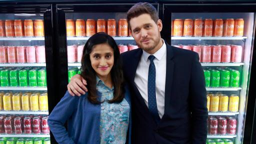 Aparna Nancherla and Michael Bublé standing in front of coolers of drinks.