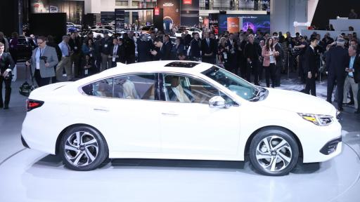 Side profile of a white 2020 Subaru Legacy surrounded by people and photographers.