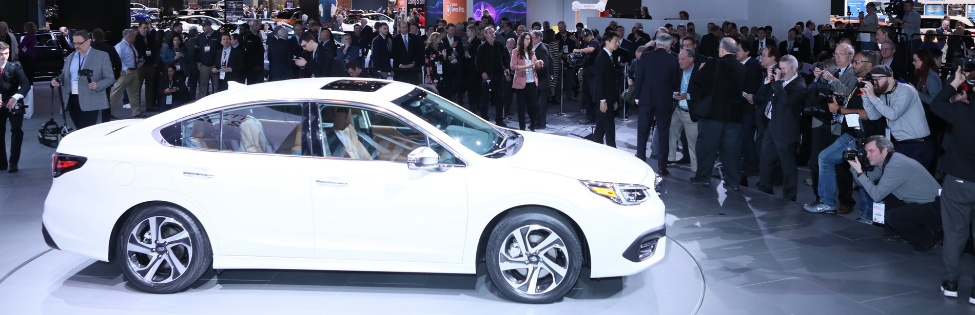 A white 2020 Subaru Legacy surrounded by a crowd and photographers.