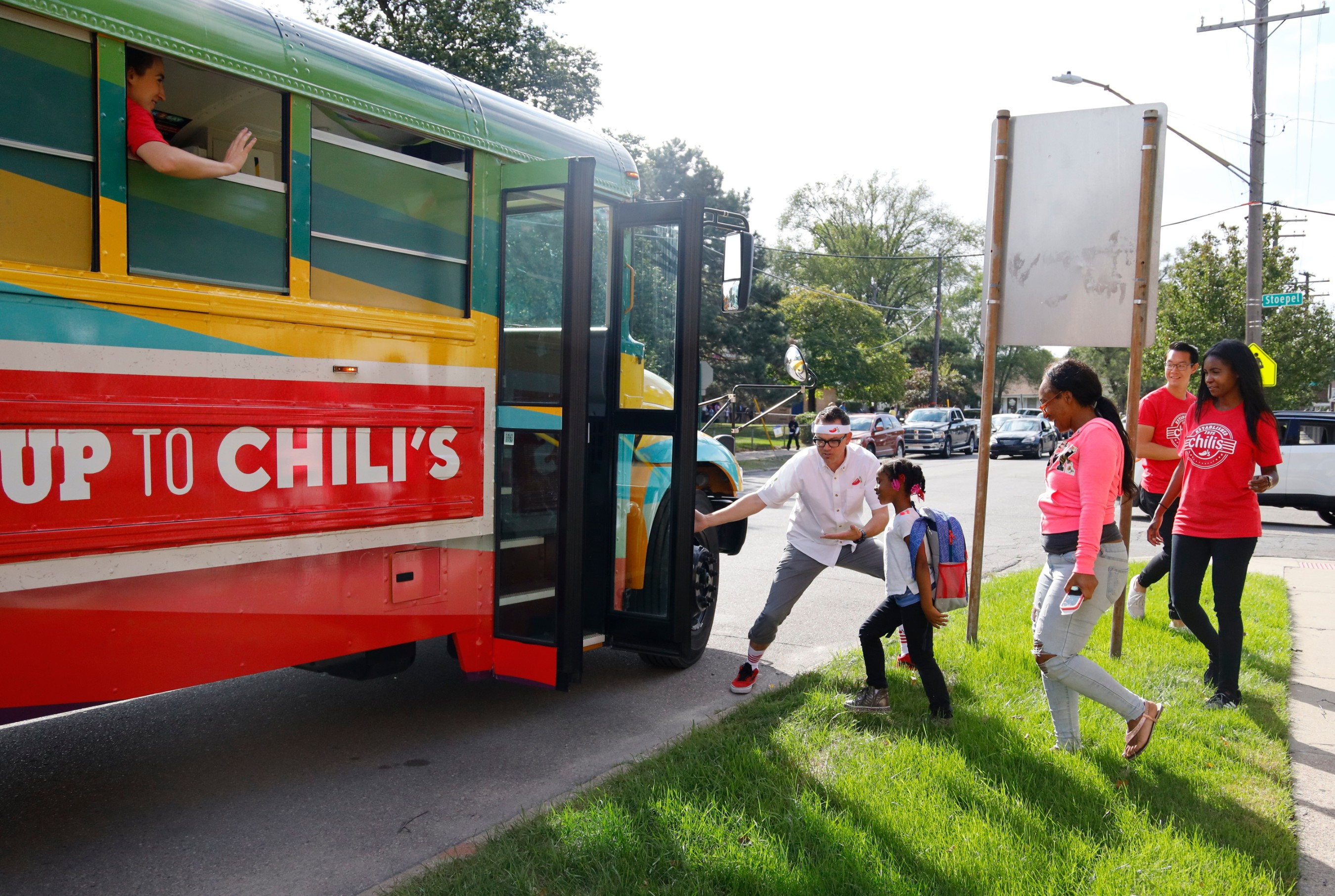 Chili's welcomes loyalty families onto the custom school bus.