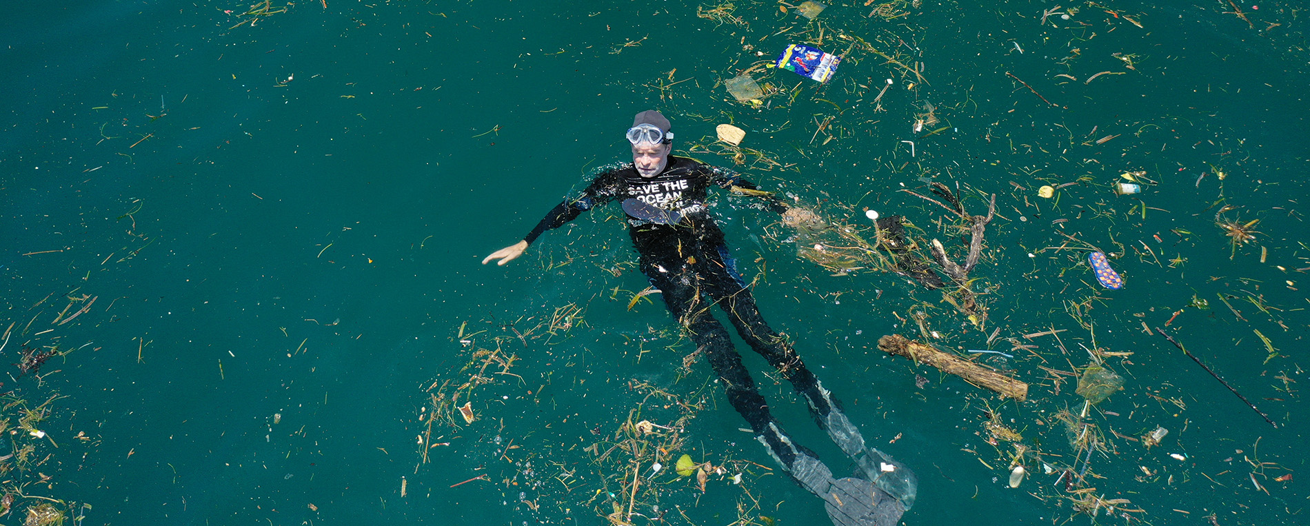 Fisk Johnson floating in the ocean surrounded by plastic debris