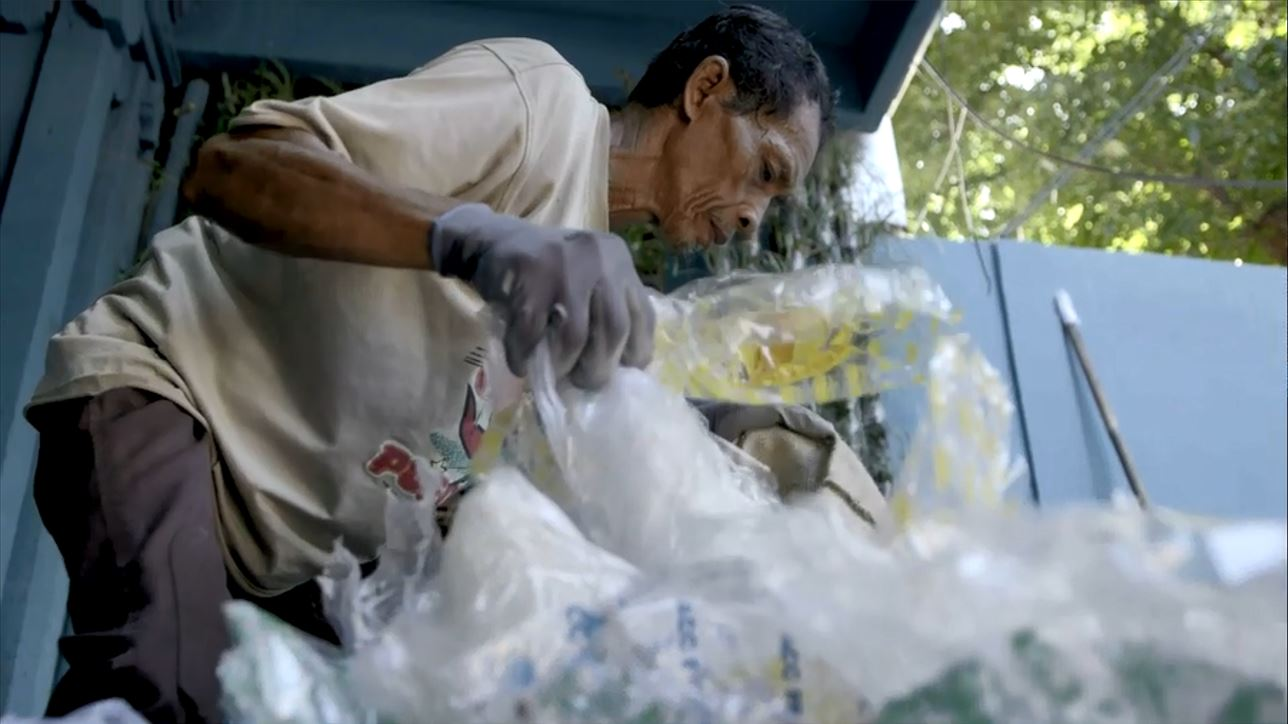 Community members in Indonesia bring in the plastic they collect for digital tokens in exchange for local goods and services