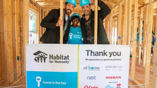 "Three workers with Habitat for Huamnity standing behind sign inside under construction house they built displaying ""Home Is The Key"" and all the generous partners, including at home, chico's, nest, Nissan, O-Cedar, HGTV, and iHeart Radio."