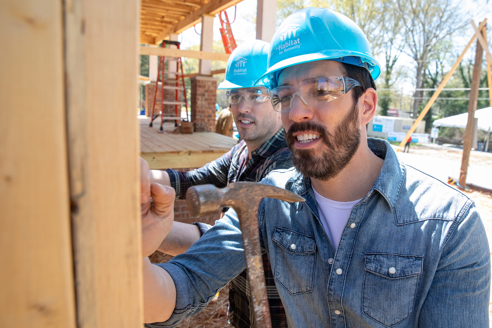 Habitat Humanitarians Drew and Jonathan Scott help install siding on a Habitat for Humanity house in Atlanta during the Home is the Key campaign launch.