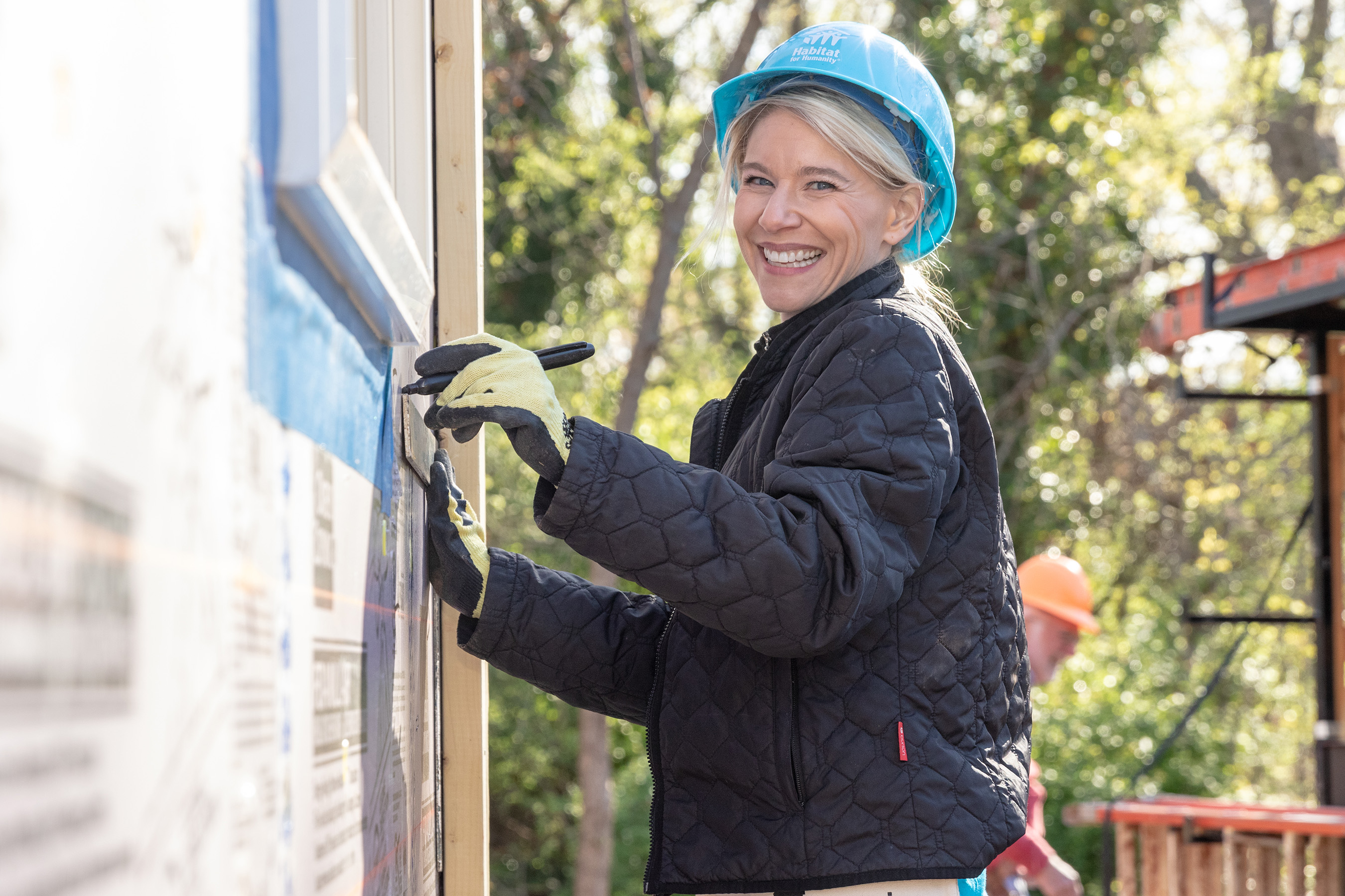 A volunteer with Chico's FAS, Inc., installs siding on a Habitat home at the launch of the Home is the Key campaign in Atlanta.