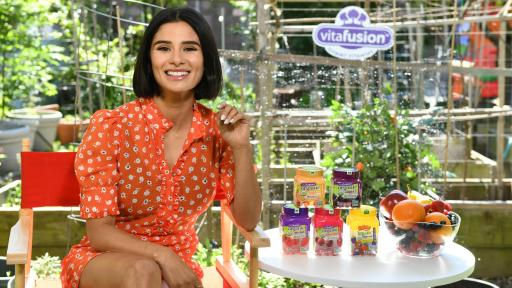 Actress Diane Guerrero Joins vitafusion™ sits on a chair by a table with vitafusion products
