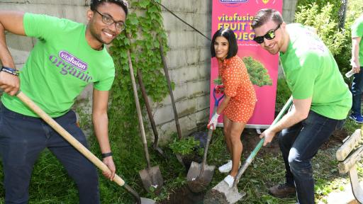 Diane Guerrero and two other people hold shovels digging a whole for a tree.