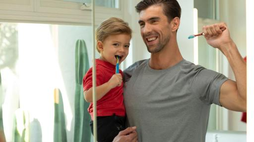 Boomer (a young child) and Michael Phelps brush their teeth