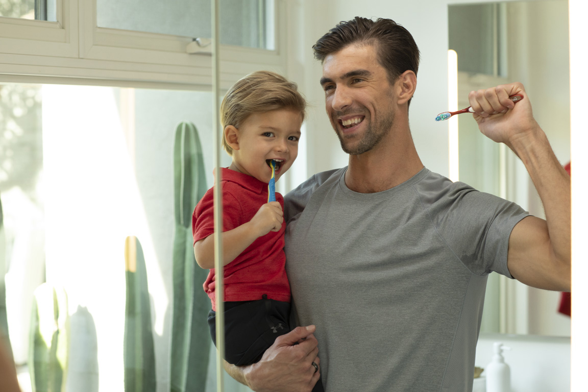 Michael Phelps teaches son Boomer (2) to turn off the faucet when brushing his teeth in support of Colgate's Save Water program.