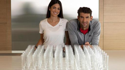 Nicole and Michael Phelps sit in front of empty glasses