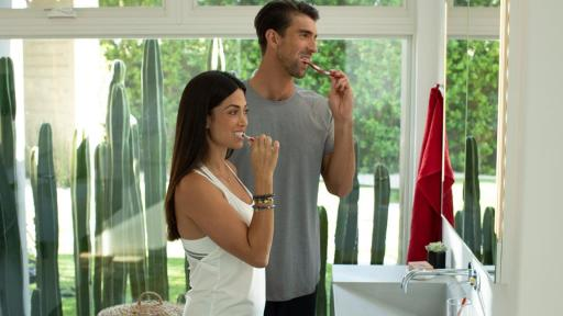 Nicole and Michael Phelps brush their teeth.