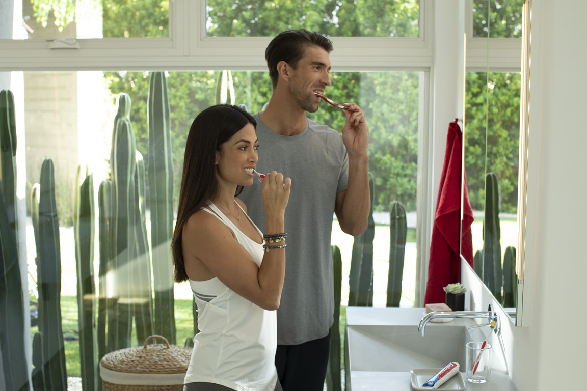In support of Colgate's Save Water program, Nicole and Michael Phelps demonstrate the importance of turning off the faucet when brushing, which can save up to four gallons of water each time.