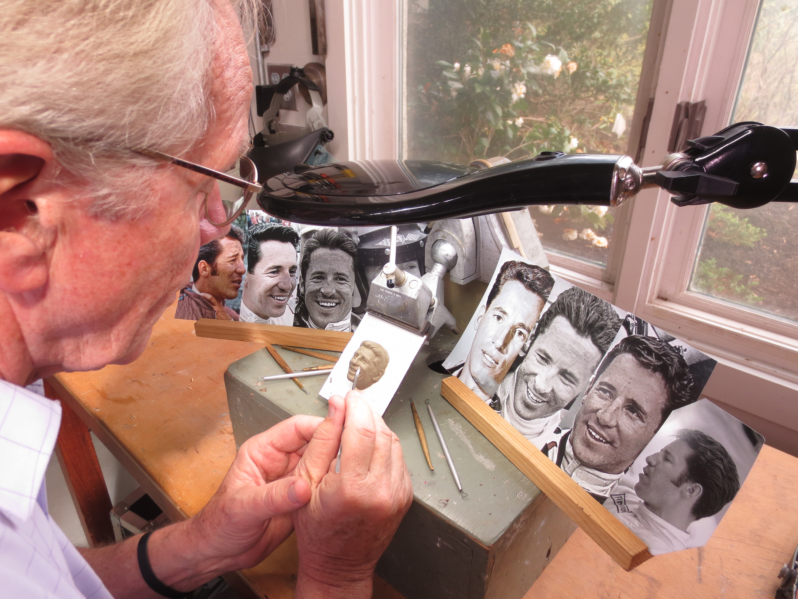 Sculptor William Behrends sculpts Mario Andretti's face from photographs for the Baby Borg trophy