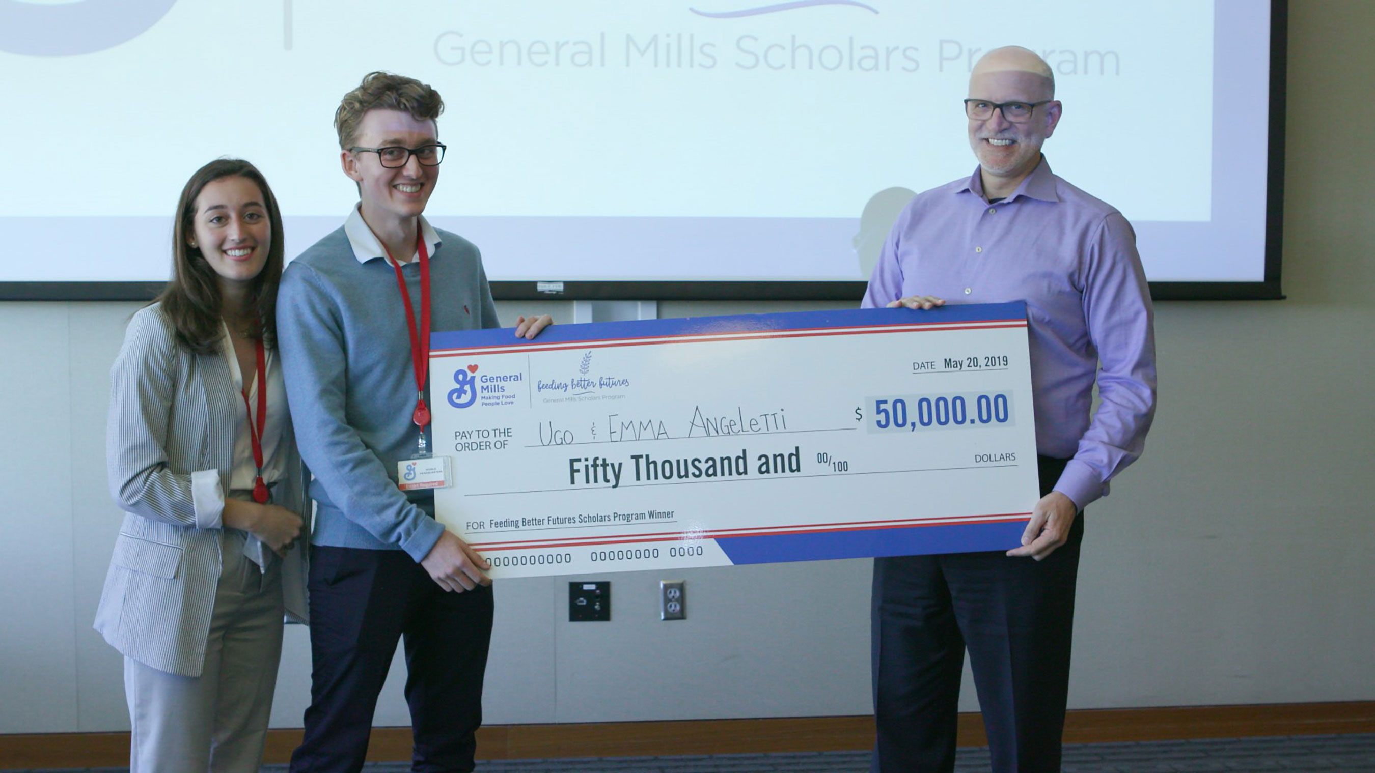 Jeff Harmening, CEO and chairman of General Mills, presents $50,000 to Ugo and Emma Angeletti