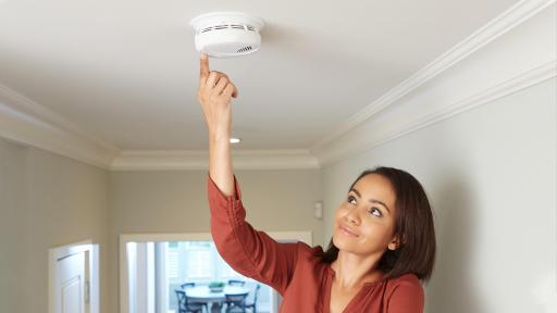 Woman testing a smoke alarm