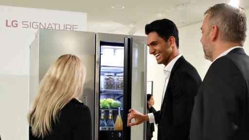 Man showing others LG refrigerator