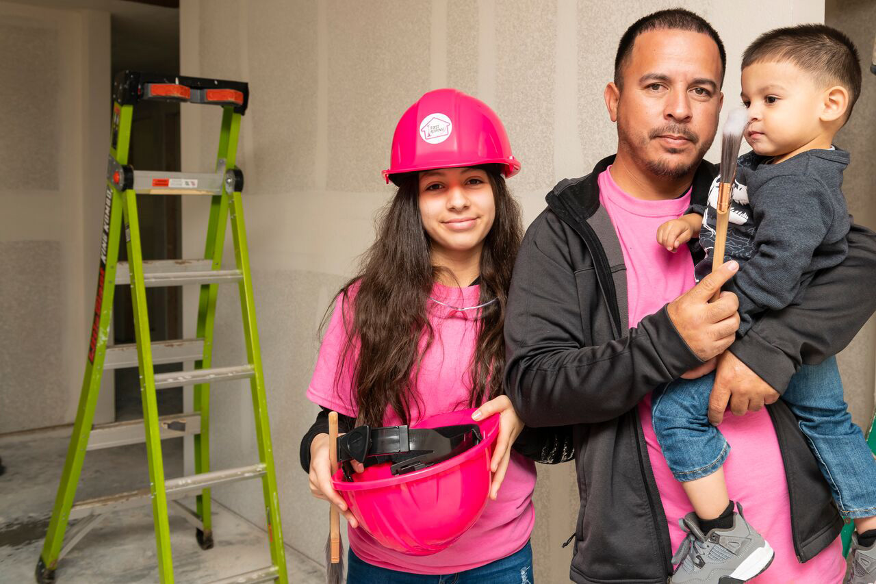 Mr. Casas and his children getting involved in the painting day with First Response™ and Habitat for Humanity.