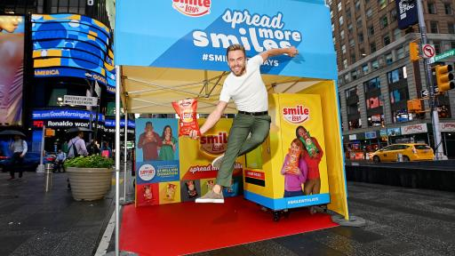 Man jumping in front of the kiosk with a bag of chips.