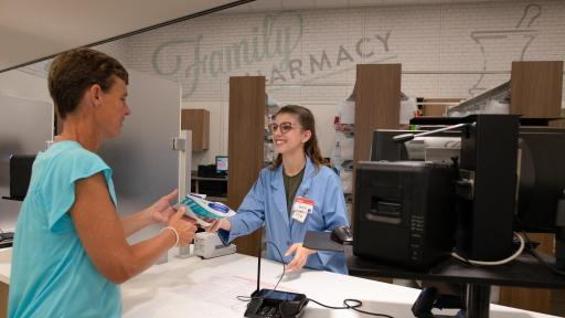 A pharmacist hands a man prescriptions
