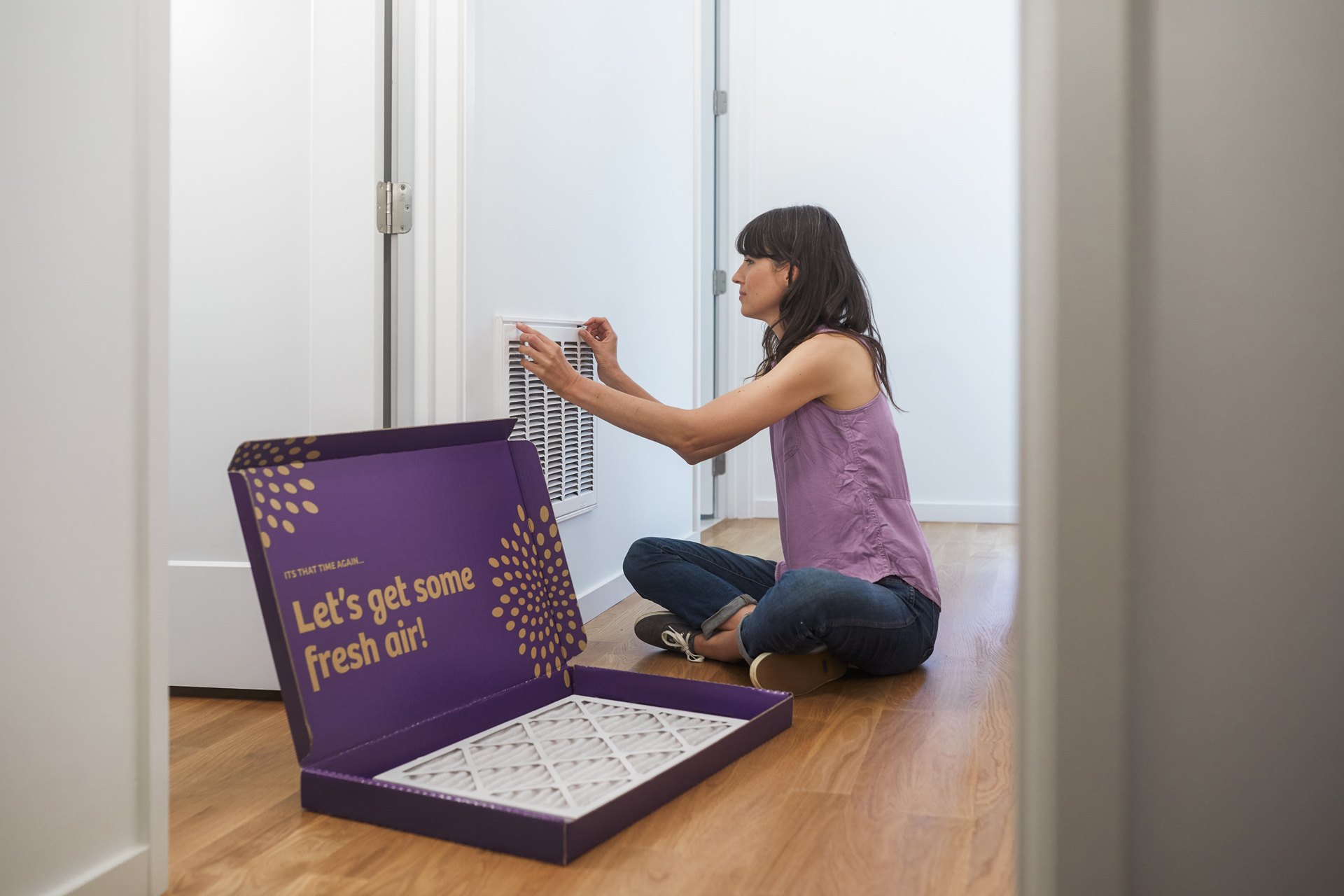 Woman changing the air filter in her house and replacing it with a new filter from SecondNature.