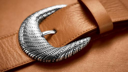 Close up of a silver buckle on brown leather
