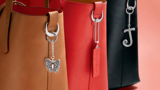 Three handbags with accessories on their handle.