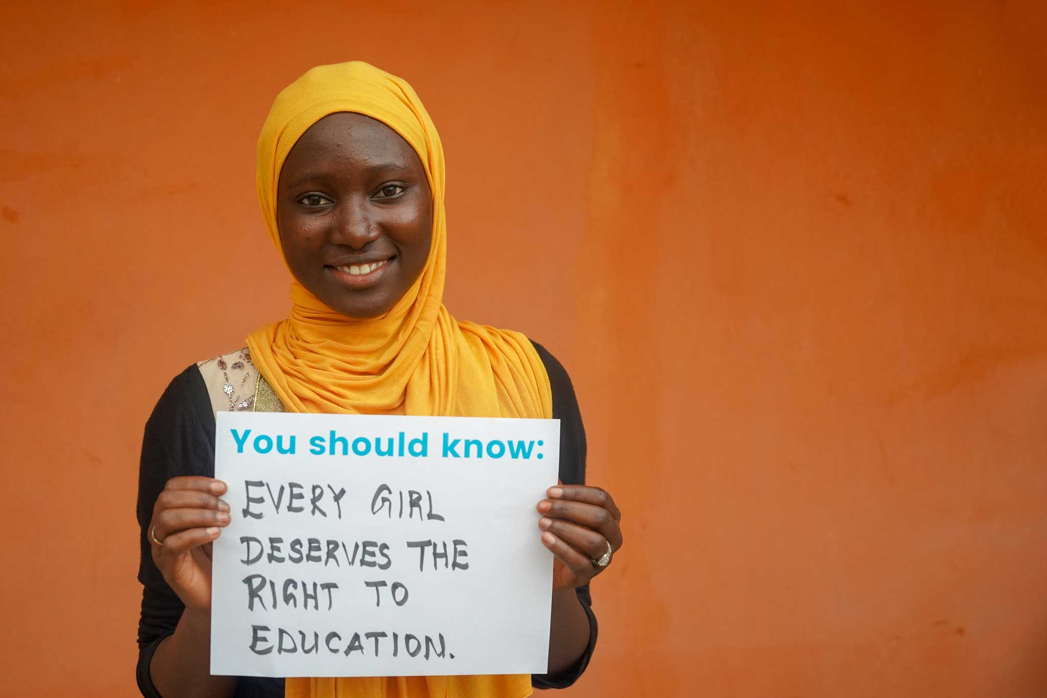 Ramatoulie, a secondary school student from Starfish International in The Gambia, holds up the right deemed most important to girls in the Global Girls' Bill of Rights. (Photo by Rene Moses Ceesay)