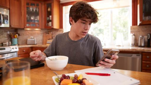 Person texting while eating breakfast