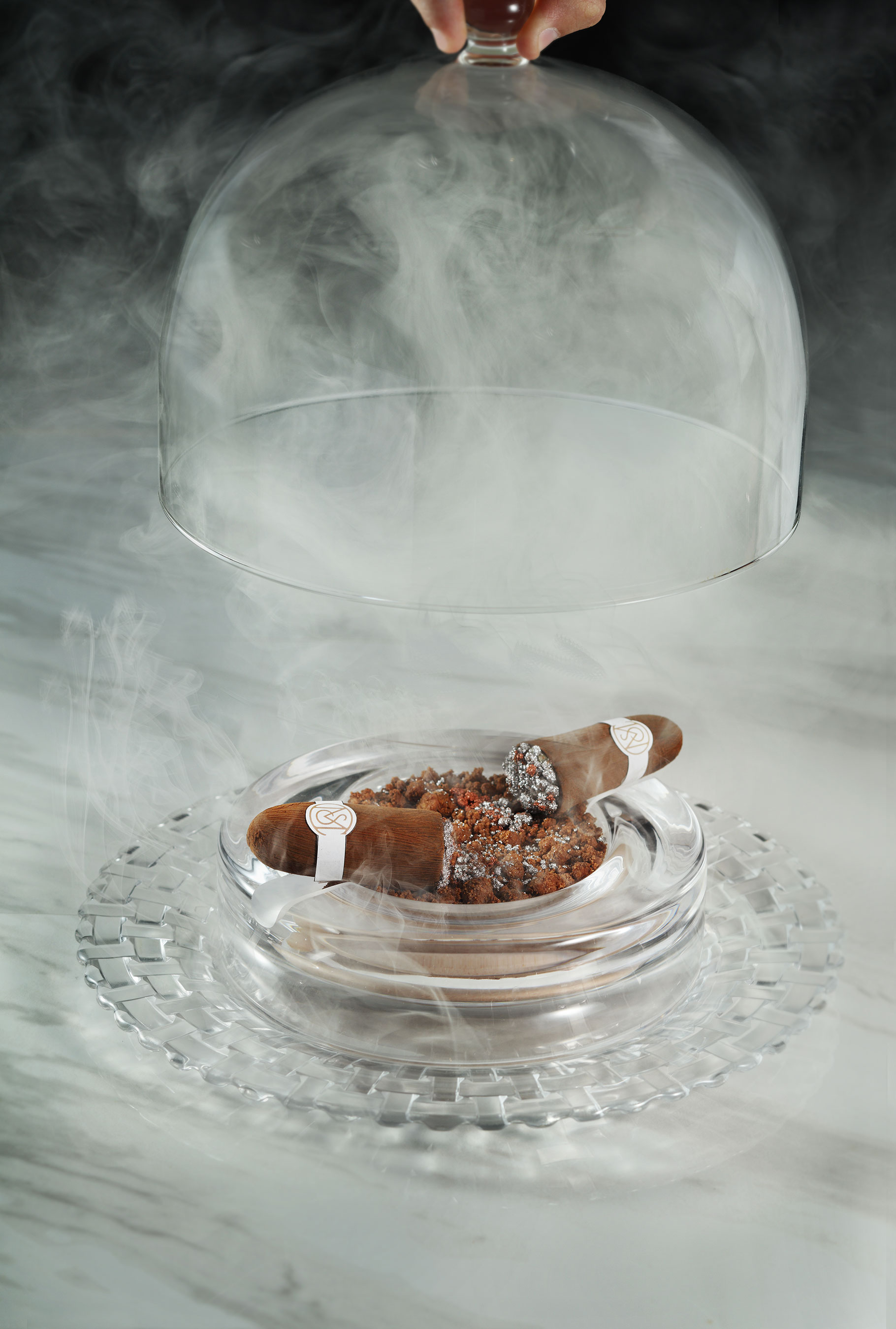 The CIGAR, The Mayfair Supper Club's edible chocolate and hazelnut dessert showpiece arrives hickory-smoked under a glass cloche.