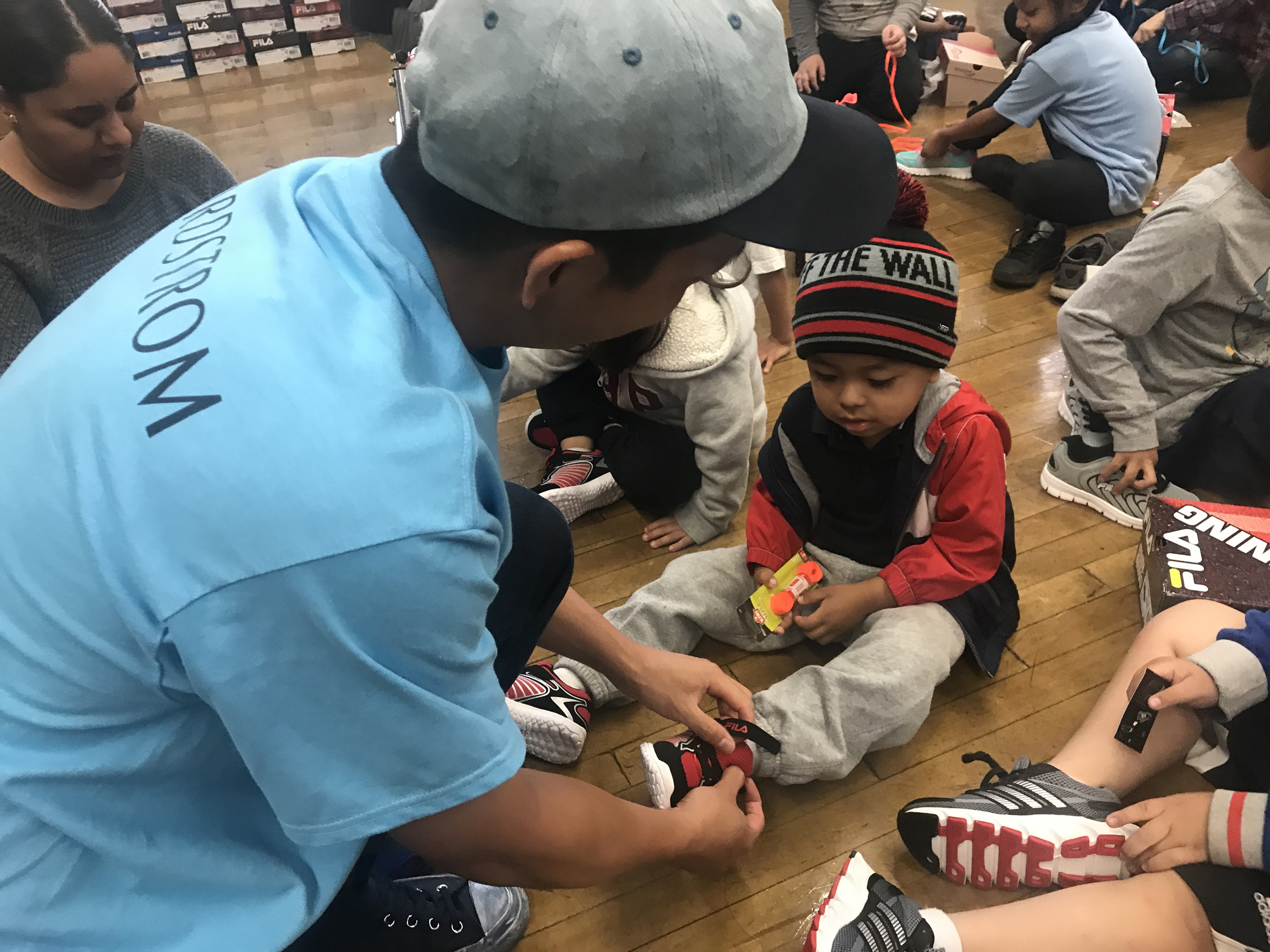 Nordstrom employee helps student try on their new shoes and makes sure they fit at shoe delivery event in 2019.