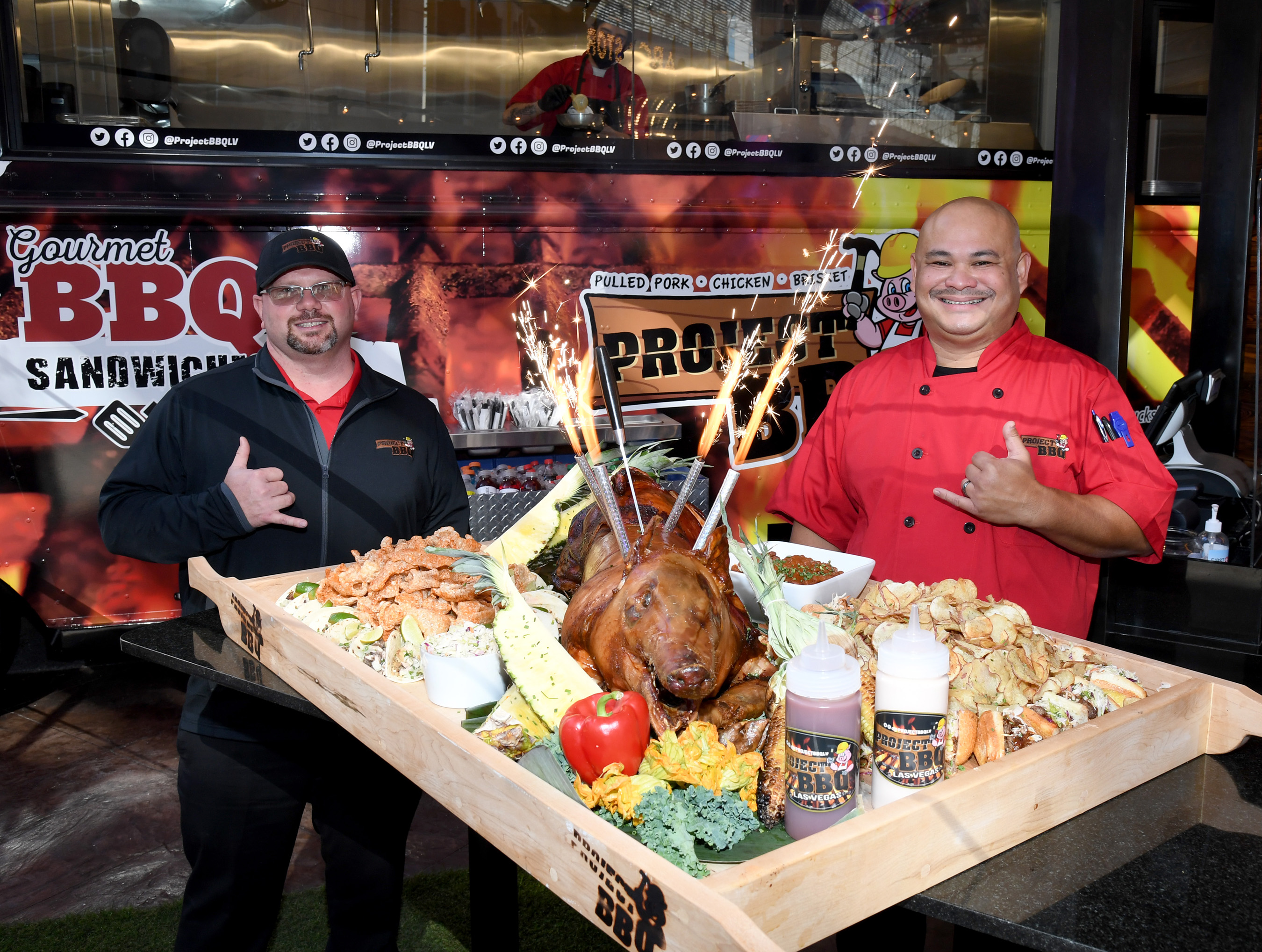 """Rob Baker and Chef Rex Bernales present the """"Hogstravaganza"""" in front of Circa's Project BBQ, serving up authentic Carolina barbecue with a Vegas twist."""
