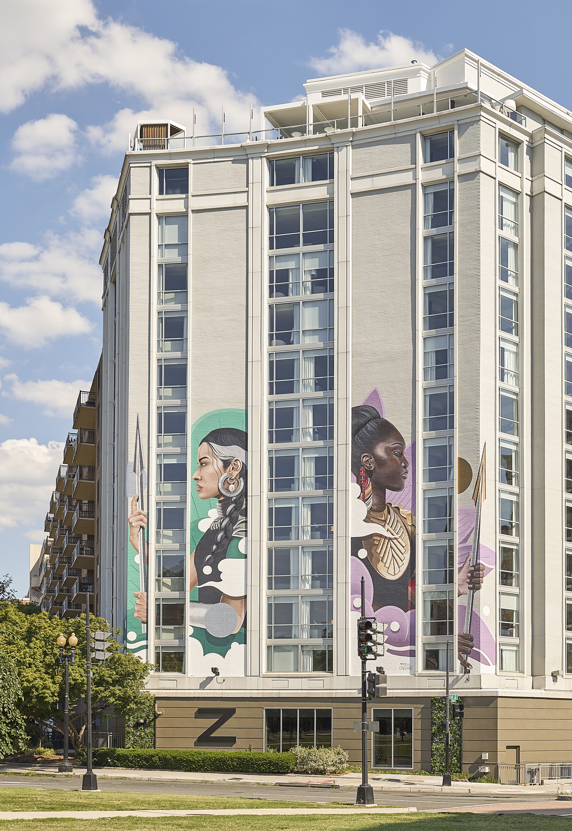 A seven-story-tall mural by MISS CHELOVE, fierce yet curious warrior-sentinel women guard Hotel Zena. Photo Credit: Mike Schwartz Photography