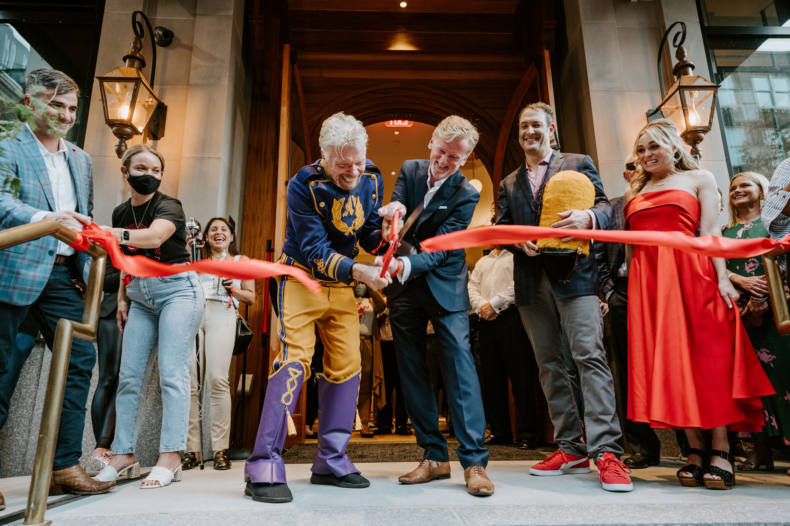Pictured left to right:  Virgin Group founder Sir Richard Branson Virgin Hotels Chief Executive Officer James Bermingham cut the ribbon to celebrate the grand opening of Virgin Hotels New Orleans while Dave Pollin of Buccini/Pollin Group looks on.
