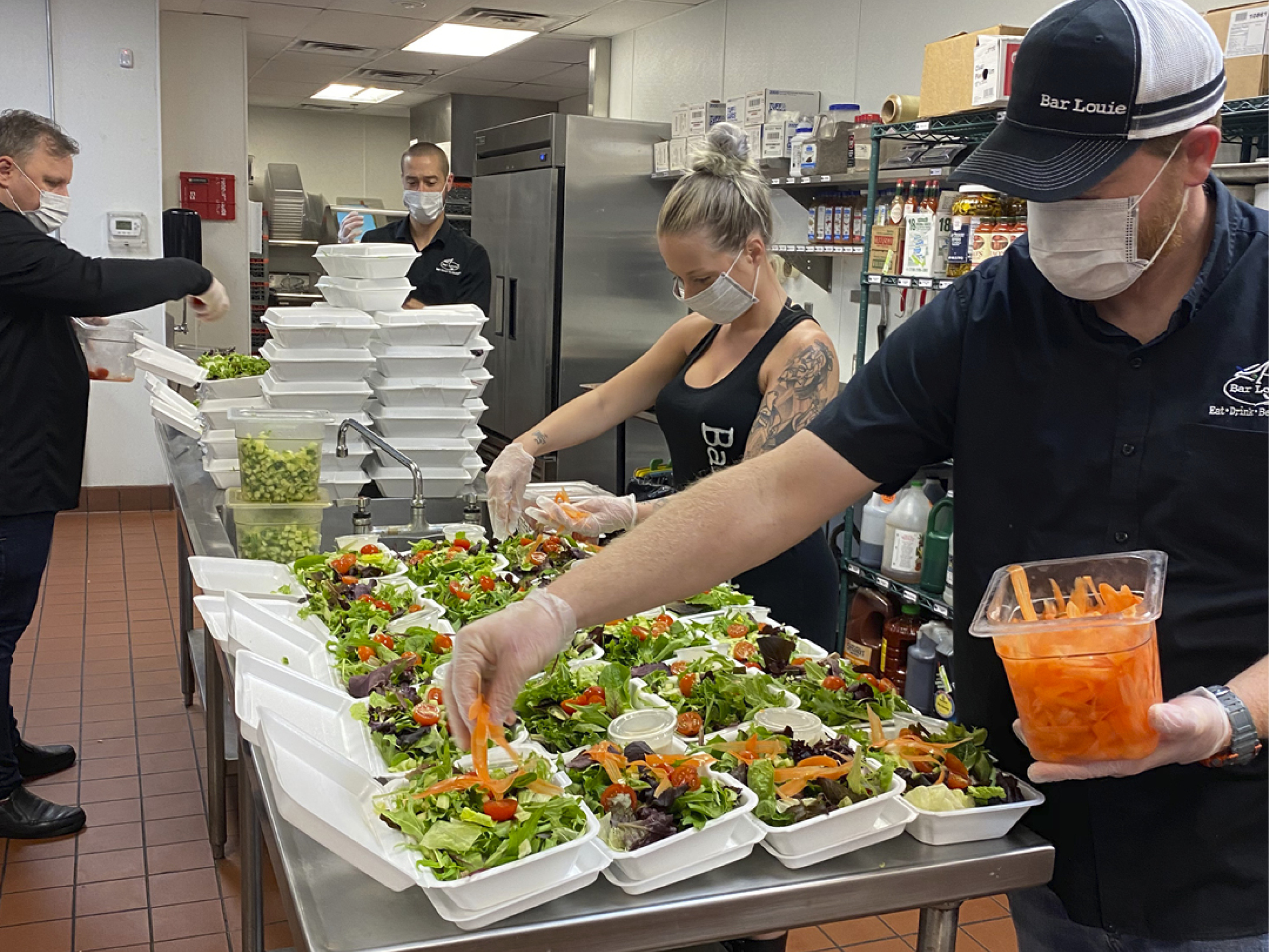 Bar Louie team members preparing meals to deliver to local front-line workers in the midst of COVID-19.