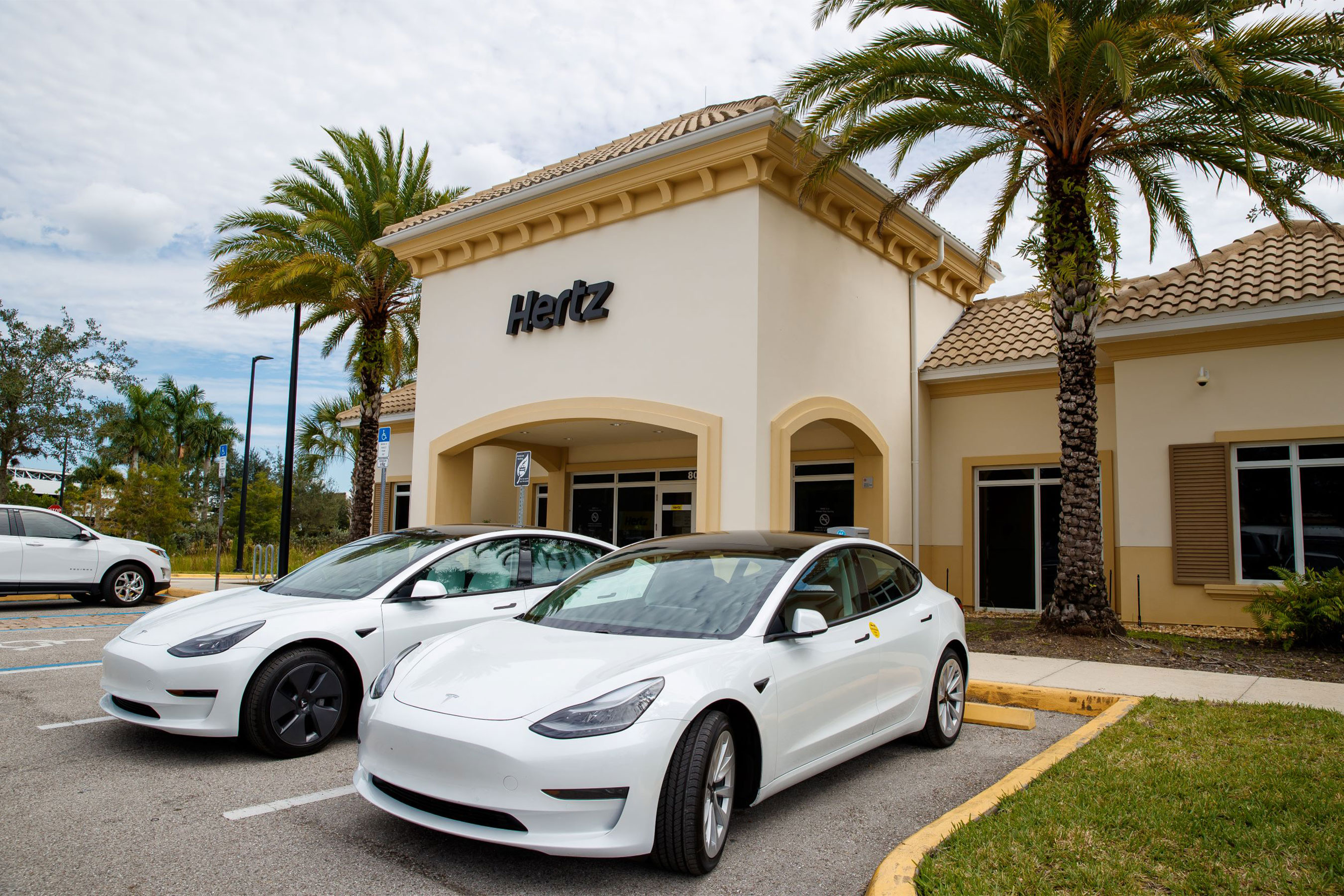 Tesla Model 3 electric vehicles at a Hertz neighborhood location.