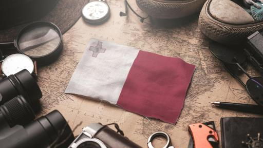Image of Malta flag, travelers accessories, an old vintage map - tourist destination concept.